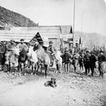 Photograph of a group of men assembled on the main street of Barkerville, preparing to leave on gold escort, 1865