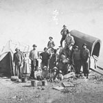 Photograph of a group of men, women and children near a tent and a covered wagon, circa 1873
