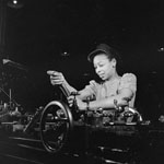 Photograph of a woman, Cecilia Butler, working on machinery in a munitions plant, Toronto, 1943