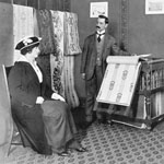 Photograph of a salesman in a wallpaper store showing samples to a lady sitting on a chair, Montréal, Quebec, circa 1912
