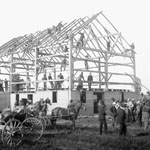 Photograph of a group of men participating in a barn raising, unknown location, June 2, 1908