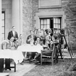Photograph of press photographers standing and sitting around a table, unknown location, unknown date